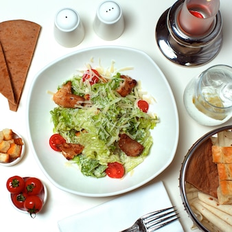 Een bovenaanzicht gekookte groenten met vlees segmenten samen met rode tomaten en sneetjes brood op de witte tafel
