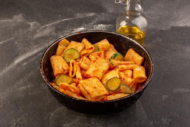 Een bovenaanzicht gekookte italiaanse pasta met tomatensaus en komkommer in de pan op de donkere tafel
