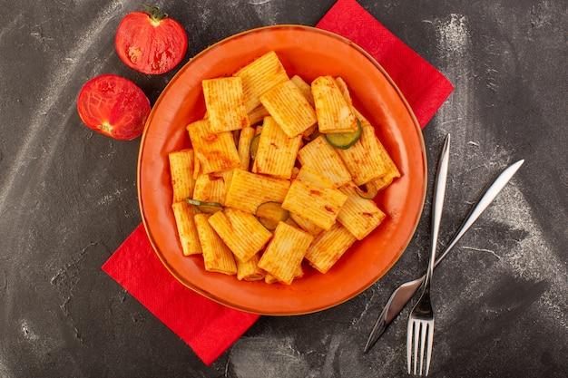 Een bovenaanzicht gekookte italiaanse pasta met tomatensaus en komkommer in plaat