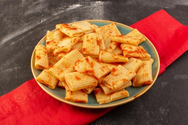 Een bovenaanzicht gekookte italiaanse pasta met tomatensaus in de plaat op de donkere tafel