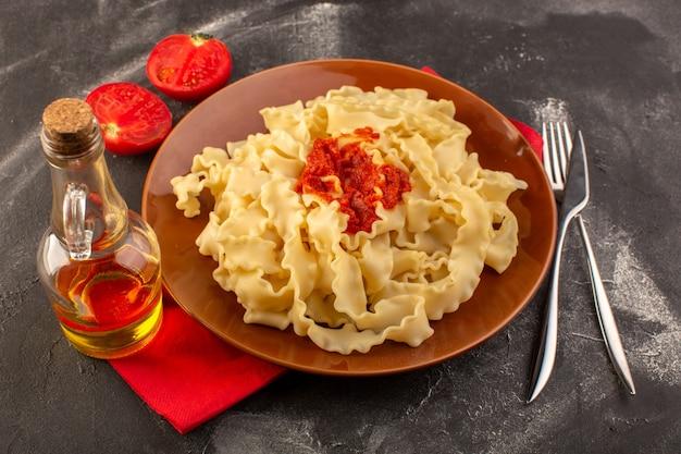 Een bovenaanzicht gekookte italiaanse pasta met tomatensaus in plaat met bestek en tomaten op de grijze tafel
