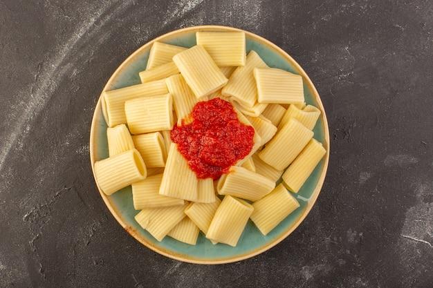 Een bovenaanzicht gekookte italiaanse pasta met tomatensaus in plaat