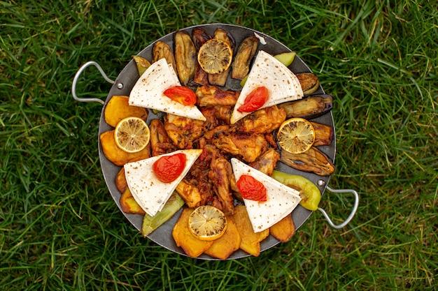 Een bovenaanzicht gekookte maaltijd met vlees en groenten in de pan op het groene gras