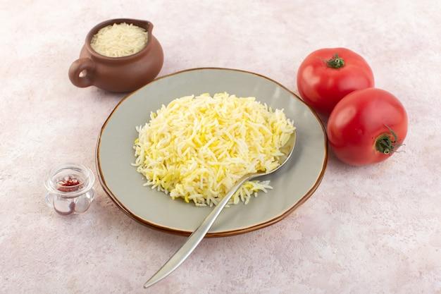 Een bovenaanzicht gekookte rijst in plaat met rode tomaten op de roze groente van de de maaltijdrijst van het bureauvoedsel