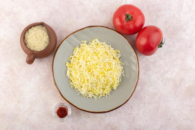Een bovenaanzicht gekookte rijst met kruiden en verse rode tomaten op de roze groenten van de het voedselmaaltijd van het bureau