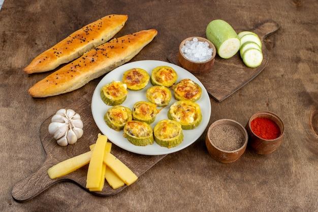 Een bovenaanzicht gekookte ronde pompoen in witte plaat met verse pompoenen, zout, kaasbrood en knoflook op het houten bureau.