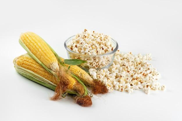Een bovenaanzicht gele likdoorns rauw met groene bladeren en verse popcorn op wit bureau, de kleurgraan van de voedselmaaltijd