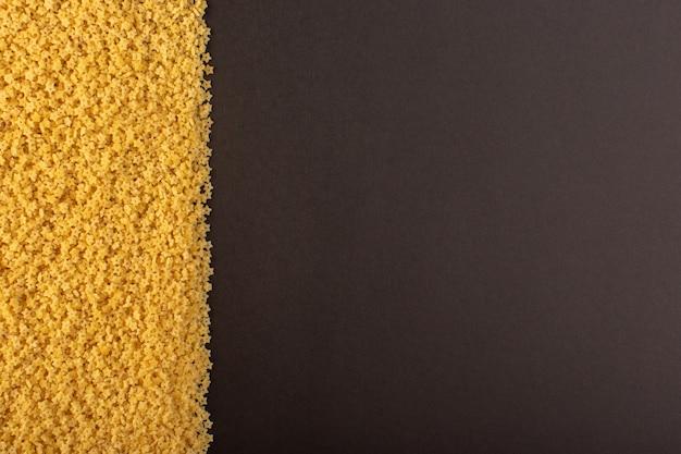 Een bovenaanzicht gele rauwe pasta aan de linkerkant donkere achtergrond voedsel maaltijd rauw eten