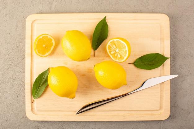 Een bovenaanzicht gele verse citroenen rijp mellow sappig met groene bladeren opgedoken op het crème bureau bekleed en gesneden op de grijze achtergrond fruit citrus kleur