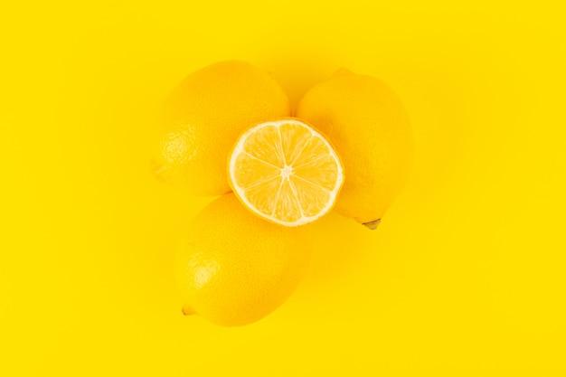Een bovenaanzicht gele verse citroenen vers rijp geheel en gesneden fruit geïsoleerd op de gele achtergrond citrusvruchten kleur