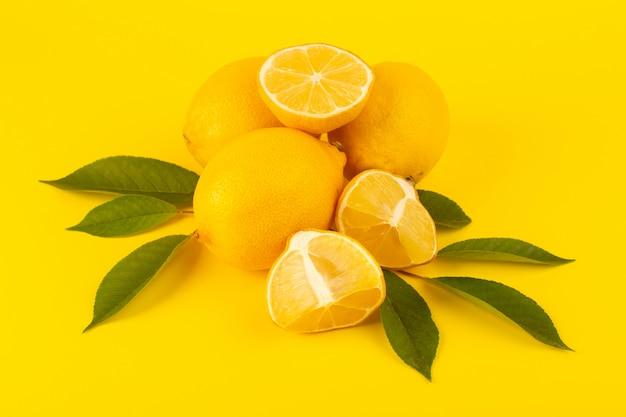 Een bovenaanzicht gele verse citroenen vers rijp geheel en gesneden samen met groene bladeren fruit geïsoleerd op de gele achtergrond citrus fruit kleur
