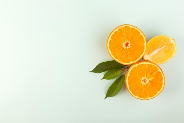 Een bovenaanzicht gesneden oranje verse rijpe sappige mellow geïsoleerde half gesneden stukken met groene bladeren op de witte achtergrond fruit kleur citrus