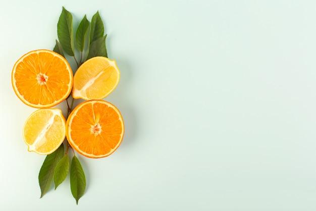 Een bovenaanzicht gesneden sinaasappel, vers, rijp, sappig, zacht, geïsoleerd, half gesneden stukjes, samen met gesneden citroenen en groene bladeren op de ijsblauwe achtergrond, fruitkleur, citrus