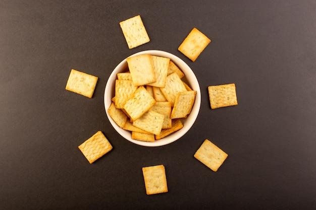 Een bovenaanzicht gezouten chips smakelijke crackers kaas binnen witte plaat op de donkere achtergrond snack zout kernachtig voedsel