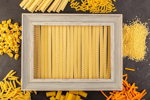 Een bovenaanzicht grijze fotolijst samen met verschillende gevormde gele rauwe pasta geïsoleerd in het donker