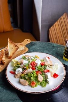 Een bovenaanzicht groentesalade met plakjes kip en brood op de groene tafel