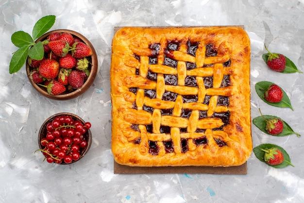 Een bovenaanzicht heerlijke aardbeientaart met aardbeigelei binnen, samen met verse aardbeien en veenbessen op de grijze bureaucake