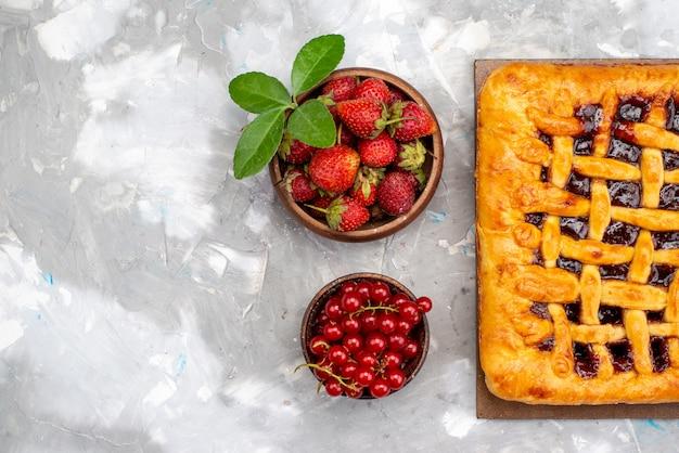 Een bovenaanzicht heerlijke aardbeientaart met aardbeigelei binnen, samen met verse aardbeien en veenbessen op het grijze dessert van de bureaucaket