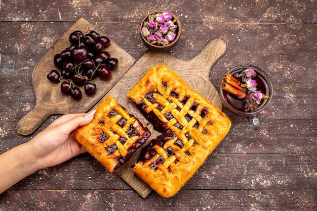 Een bovenaanzicht heerlijke aardbeientaart met aardbeigelei kersen en thee op de houten bureau cake koekje suiker bes