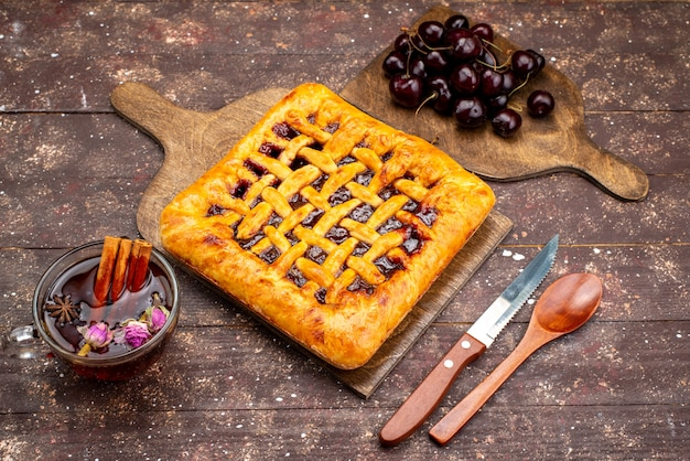 Een bovenaanzicht heerlijke aardbeientaart met aardbeigelei kersen en thee op de houten bureau cake koekjessuiker