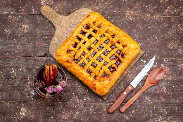 Een bovenaanzicht heerlijke aardbeientaart met aardbeigelei samen met thee op de houten koekjessuiker van het bureau