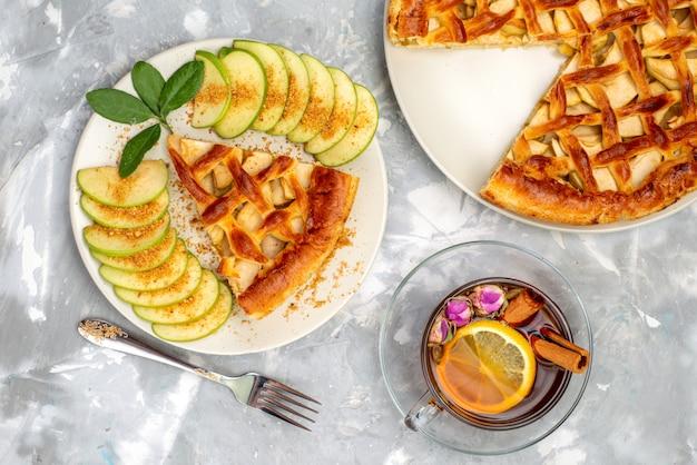Een bovenaanzicht heerlijke appeltaart in plaat met thee en verse groene appel op de grijze koekjessuiker van de bureaucake