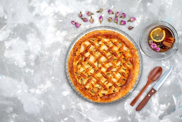 Een bovenaanzicht heerlijke appeltaart met hete thee en bloemen cake koekje suiker fruit thee