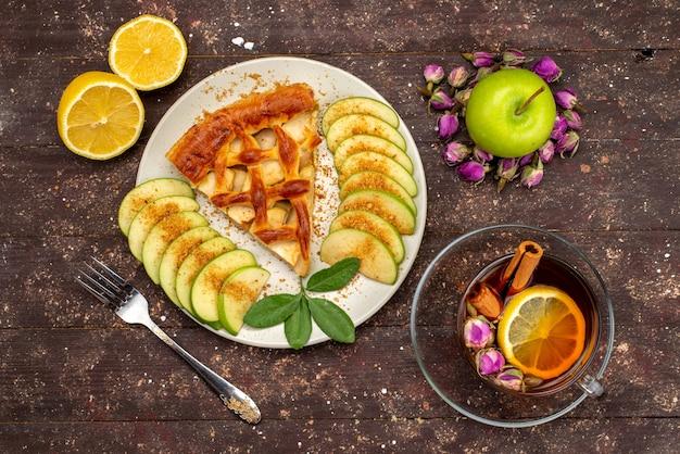 Een bovenaanzicht heerlijke appeltaart met thee verse groene appels op het houten bureau cake koekje suiker dessert