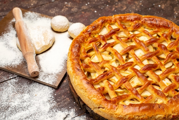 Een bovenaanzicht heerlijke appeltaart rond gevormd deeg en bloem op de donkere achtergrond cake koekje suiker fruit