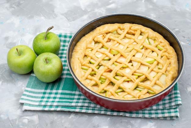 Een bovenaanzicht heerlijke appeltaart ronde gevormd in de pan met verse groene appels op het heldere bureau cake koekje
