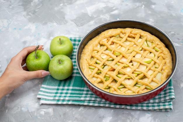 Een bovenaanzicht heerlijke appeltaart ronde gevormd in pan met verse groene appels op het lichte bureau cake koekje