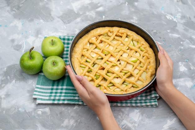 Een bovenaanzicht heerlijke appeltaartronde gevormd in de pan die de oven in gaat met verse groene appels op het lichte bureau cakekoekje