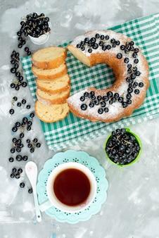 Een bovenaanzicht heerlijke cake met verse bosbessen en thee op het witte de theekoekje van de bureaucake