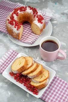 Een bovenaanzicht heerlijke cake met verse rode amerikaanse veenbessen kaneel en thee op de witte theebes van het bureaukoekje