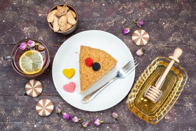 Een bovenaanzicht heerlijke honingcake met snoepjes, honing en bloemen op de donkere achtergrond caketheesuikergoed