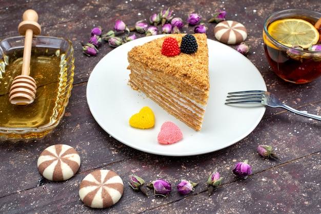 Een bovenaanzicht heerlijke honingcake met snoepjes, honing en bloemen op de donkere achtergrond