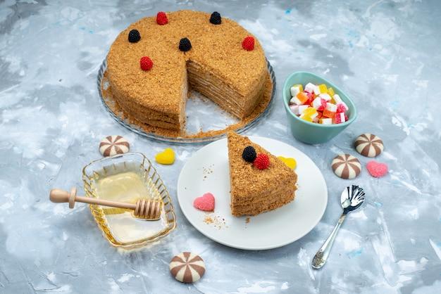 Een bovenaanzicht heerlijke honingcake met snoepjeshoning op het blauwe suikergoed van de achtergrondcake