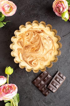 Een bovenaanzicht heerlijke koffie cake zoete chocolade heerlijke suiker bakkerij cake zoete samen met rozen op het donkere bureau
