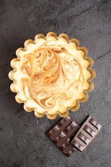 Een bovenaanzicht heerlijke koffie taart zoete chocolade heerlijke suiker bakkerij taart snoepje op het donkere bureau