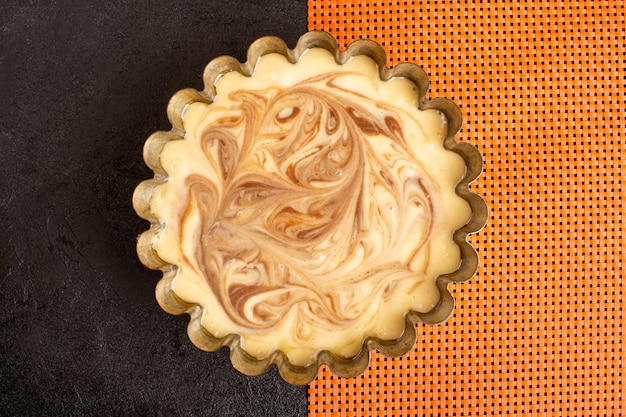 Een bovenaanzicht heerlijke koffie taart zoete heerlijke suiker bakkerij taart zoete op het donkere en oranje bureau
