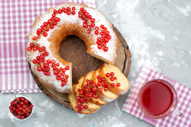 Een bovenaanzicht heerlijke ronde cake met verse rode veenbessen en cranberrysap op de witte bessensuiker van de bureaucake