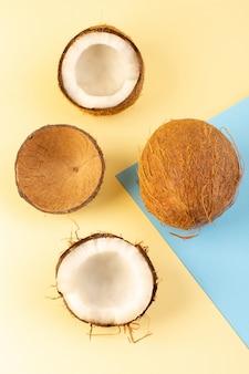 Een bovenaanzicht hele kokosnoten en gesneden melkachtig fris mellow geïsoleerd op de crème-iced-blauw gekleurd