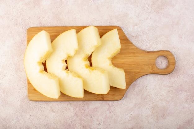 Een bovenaanzicht in stukjes gesneden verse meloen, zacht, sappig en zoet bekleed op een houten bureau