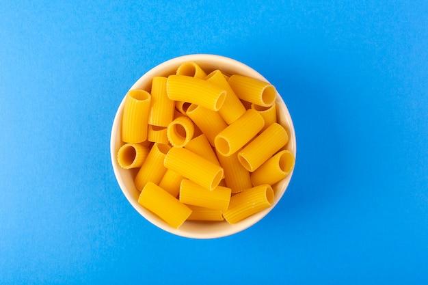 Een bovenaanzicht italia droge pasta vormde kleine gele rauwe pasta in crèmekleurige ronde kom geïsoleerd op de blauwe achtergrond italiaanse spaghetti food pasta