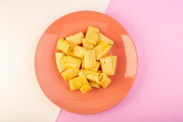 Een bovenaanzicht italiaanse pasta met gedroogde groene kruiden in roze plaat op wit