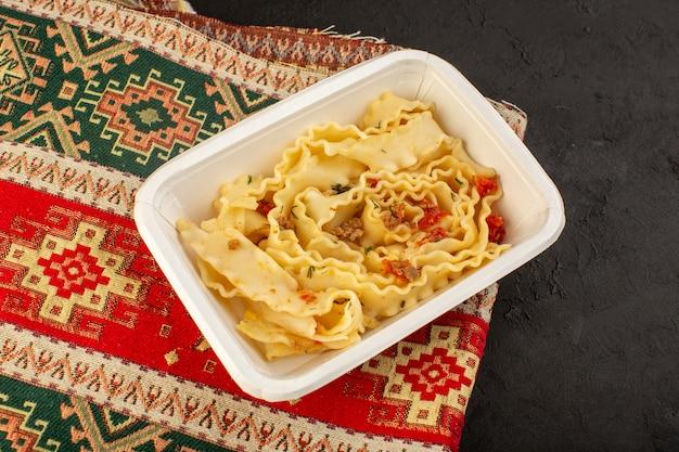 Een bovenaanzicht italiaanse pasta met tomaten in witte kom op gekleurd tapijt en donker