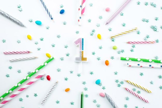 Een bovenaanzicht kaarsen en snoepjes verjaardagsdecoratie op wit bureau, verjaardagsfeestje