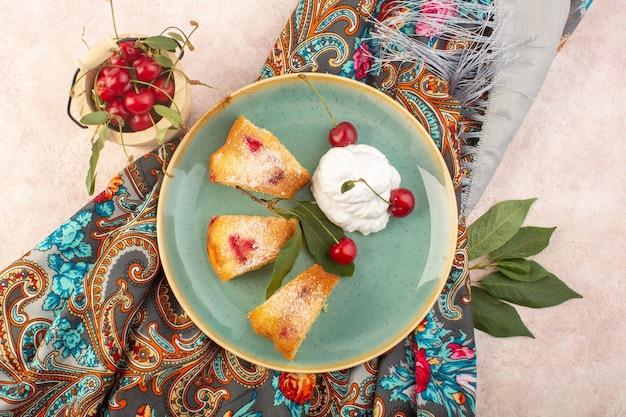 Een bovenaanzicht kersen cake plakjes binnen ronde plaat met kersen op het roze bureau cake koekje suiker zoet