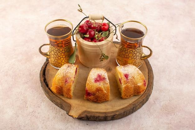Een bovenaanzicht kersen cake plakjes met kersen en thee op het roze bureau cake koekje suiker zoet