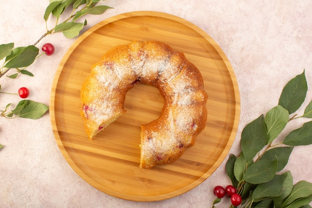 Een bovenaanzicht kersencake op het houten bureau met kersen op het roze bureau cake koekje suiker zoet